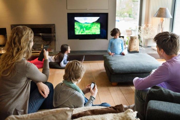 Keluarga menonton TV bersama. Sambil main gadget